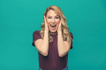 Portrait of blonde surprised emotional girl on blue background.