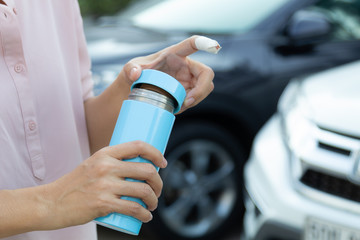 Woman hand injury holding stainless steel water cylinder with car background, concept of plastic free.