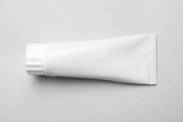 Blank tube of toothpaste on white background, top view