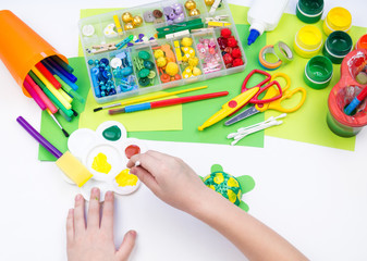 The child makes a craft toy from foam plastic tortoise. Material for creativity and education.