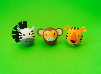 Easter holiday concept with cute handmade eggs: orange tiger and zebra,a monkey.
