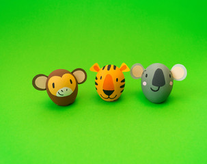 Easter holiday concept with cute handmade eggs: orange tiger and koala,monkey.