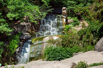 mountain waterfall with a stream of water over the stones down with green plants and trees on a sunny summer day.