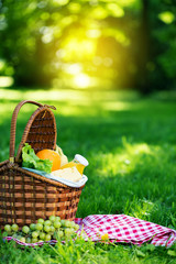 Tuinposter Picknick Picnic basket with vegetarian food in summer park