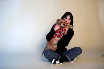 A woman poses for photographs with her pet dog at a pet studio in Seoul