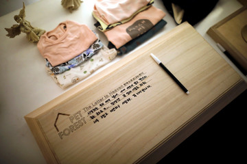 A pet owner leaves a message on top of a coffin containing the body of her dog before its cremation at a pet funeral service company in Gwangju
