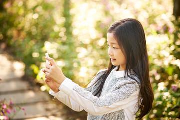 little asian girl taking a selfie using mobile phone