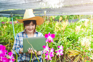 Women farmers Flower garden export abroad Standing holding a laptop Send information to customers for trading