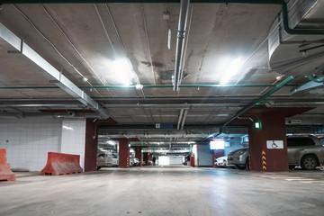 Illuminated underground car parking garage interior under modern mall with lots of vehicles