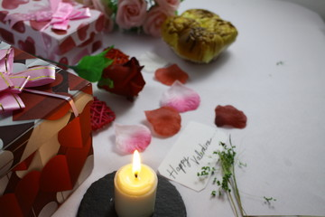 Photoshoot of rose, gift boxes, and candle burning. Valentine day
