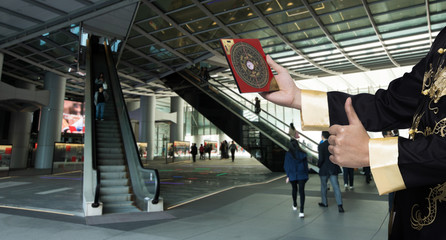 Feng Shui Master show FengShui Compass and turn direction to Force Energy, He wear black shirt to check Wind Qi flow Wealth, Luck, Prosperity inside Escalator Building, Dragon Location Position Wall mural