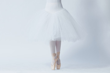 A girl stands on outstretched legs, shod in pointe shoes. A child in a white dress for dancing and white tights. Feet in pointe. Exercises in the ballet school. Ballet classes. White background.