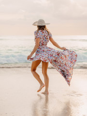 Life style woman in dress on beach at sunset or sunrise. Feminine style.