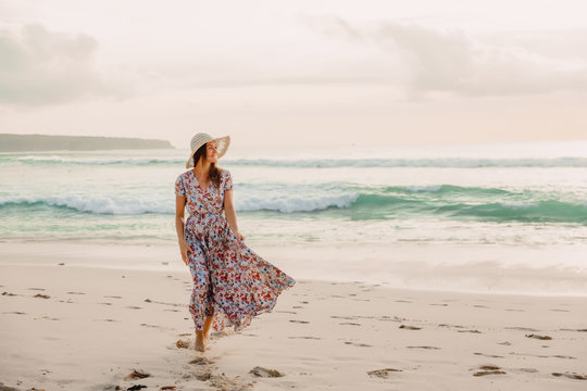 Woman in summer dress on beach at sunset or sunrise. Woman and ocean