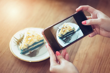 young woman holding smartphone take photo cake on wooden table in cafe