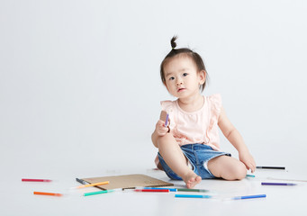 Asian little girl being painted, in white background