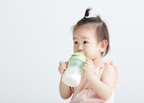 Cute Asian girl drinking milk with a bottle. On white background