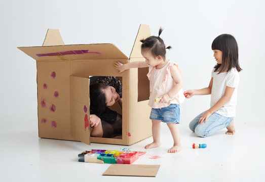 Asian mother and daughter playing together in paper house, on white background