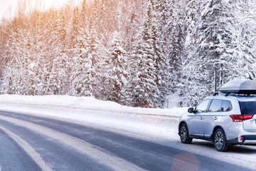 Suv car with rooftop cargo carrier trunk stay on roadside of winter road. Family trip to ski resort. Winter holidays adventure. car on winter road