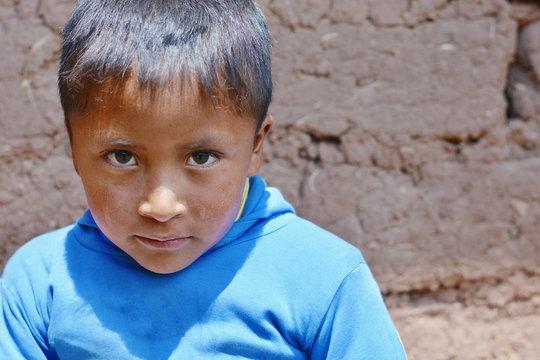 Sad little latin american boy outside.