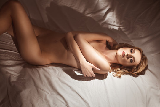 Top view of a sensual young woman lying naked or nude in the morning sunlight