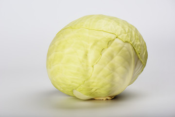 Raw green cabbage isolated on light gray background.