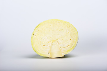 An incision of ripe green cabbage isolated on a light gray background.