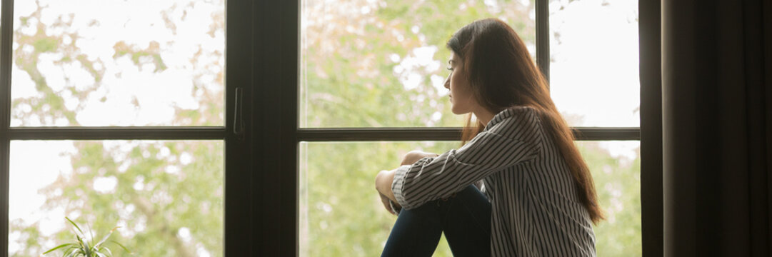 Horizontal photo one teen lonely woman sitting at home on sill look at window feels sad depressed frustrated thinking about problem panoramic banner for website header design with copy space for text.
