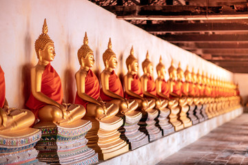 Row of golden meditation buddha sitting figures statues inside corridor  is lined up at Wat Phutthaisawan, Phra Nakhon Si Ayutthaya, the worship of Buddhism in Thailand,