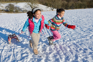 Two excited girls on winter vacation pulling sled up snowy hill