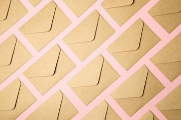 kraft brown paper envelopes on pink background
