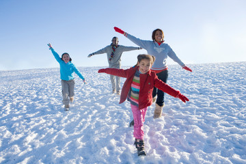 Family on winter vacation running down snowy hill smiling at camera