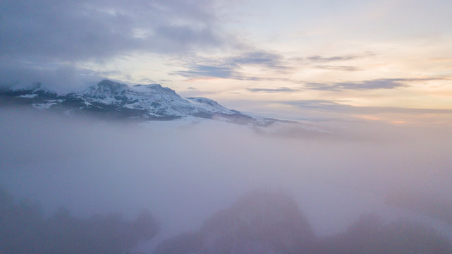 Aerial mountain winter landscape. Fantastic morning clouds glowing by sunlight.