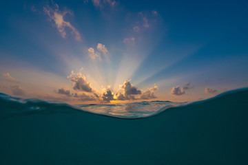 Beautiful sunset in tropical water with waterline and sunrays on background