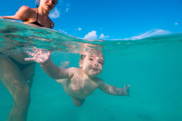 Happy mother playing with infant boy in beautiful tropical sea water with white sand, activity in vacation, underwater shot at Maldives, baby diving underwater