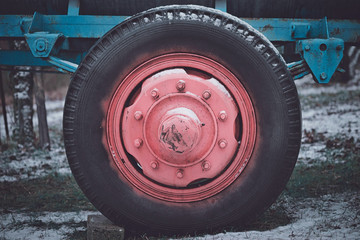 Old red wheel rim with black tire in winter