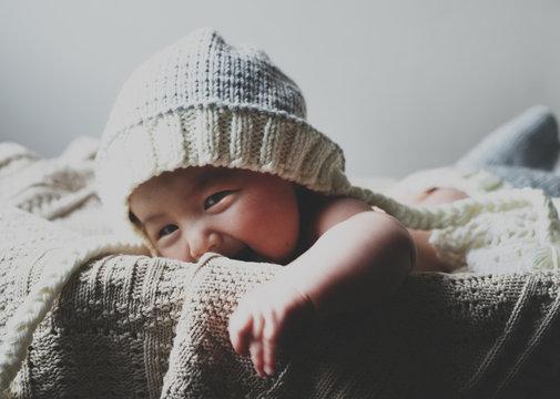 Portrait of smiling baby boy wearing knit hat lying in basket