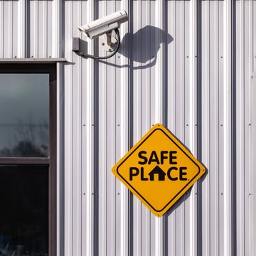 Safe place sign of a light metal wall of a building with a CCTV security cam above it.