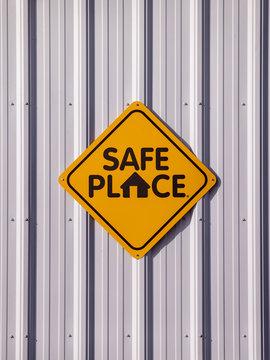 Safe place sign of a light metal wall of a building.