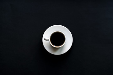 top view of white cup of coffee on black background. Minimal flat lay. Wall mural