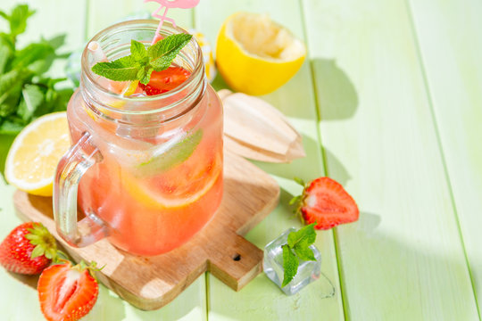 Summer strawberry lemonade with lemon and ice, copy space