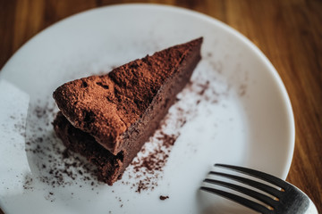 One slice of vegan chocolate brownie cake on wooden table. Sugar free, wheat free, dairy free, flourless dessert. Dark mood food photo. Healthy eating, lifestyle concept. Copy space