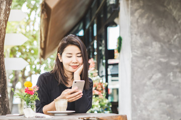 beautiful Asian woman using smart phone and drinking coffee in cafe