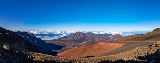 Scenic panorama of a Haleakala volcano from Keonehe'ehe'e trail overlooking cinder cones inside a caldera. Clear blue sky white puffy clouds below the horizon and rich red-brown colors of a mountain
