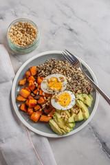 Quinoa salad in bowl with avocado