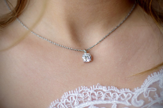 Morning gathering of the bride. Suspension on the neck. Beautiful neckline. Close-up.