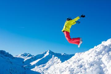 Girl snowboarder jumping and having fun in the winter ski resort.