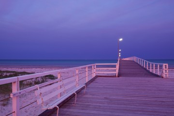 Photo of a jetty or pier with orange pink backlighting from a morning sunrise
