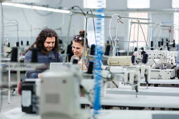 Adult woman and young man working with computer in textile factory.