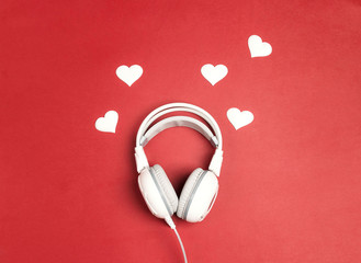 White headphones with heart on red background. Romantic music concept.